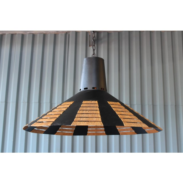 1960s French industrial saucer light, recently rewired and finished in matte black. We added a rattan detail along the...