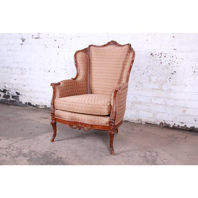 A gorgeous antique French carved wingback lounge chair, circa 1930s. The chair features a solid walnut frame with...
