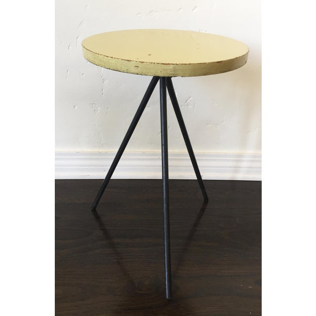 Wrought Iron and solid birch wood top painted a long time ago a beautiful Jean Prouvé yellow. Made in the 1950s.