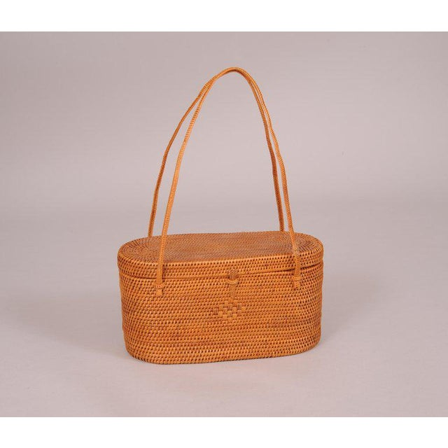 "This beautifully hand woven straw bag is an oval shaped box bag from the 1950's. The top is attached with straw ""hinges""..."