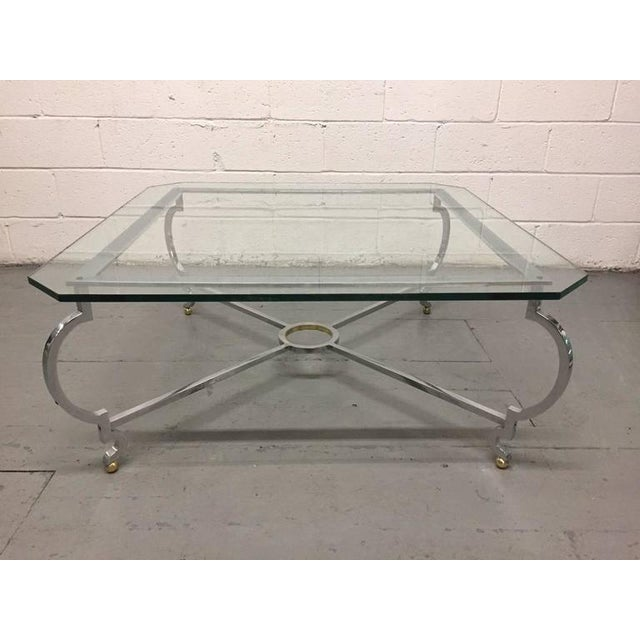 Polished steel and brass coffee table. Stretcher has curved legs with brass ball feet.