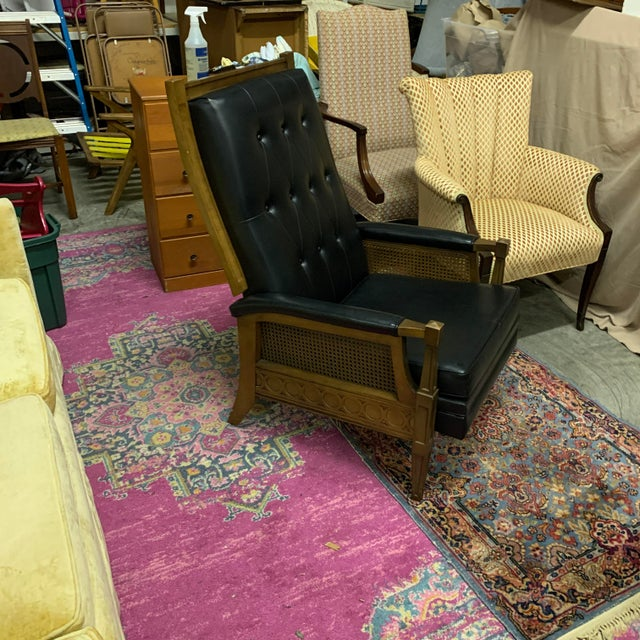 Vintage black Naugahyde and wooden recliner with caning accents on the arms in a toned down Spanish/Italian Regency style...