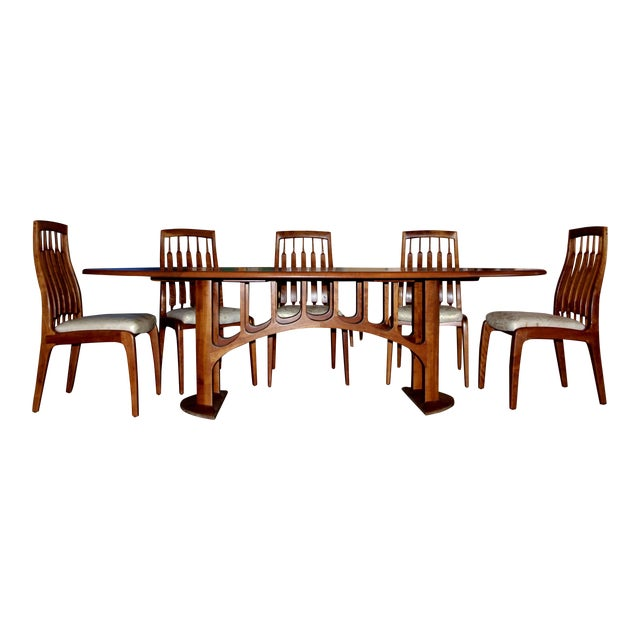 A custom-made sculptural dining table with eight chairs custom-made by the noted California Craftsman Randy Bader. The...