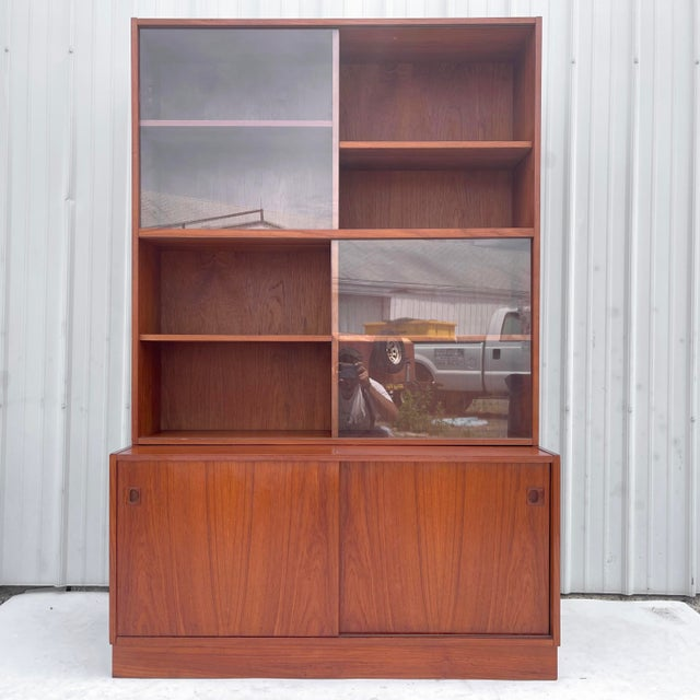 Impressive Danish Modern bookshelf features lower teak cabinet with shelved storage behind sliding doors combined with...
