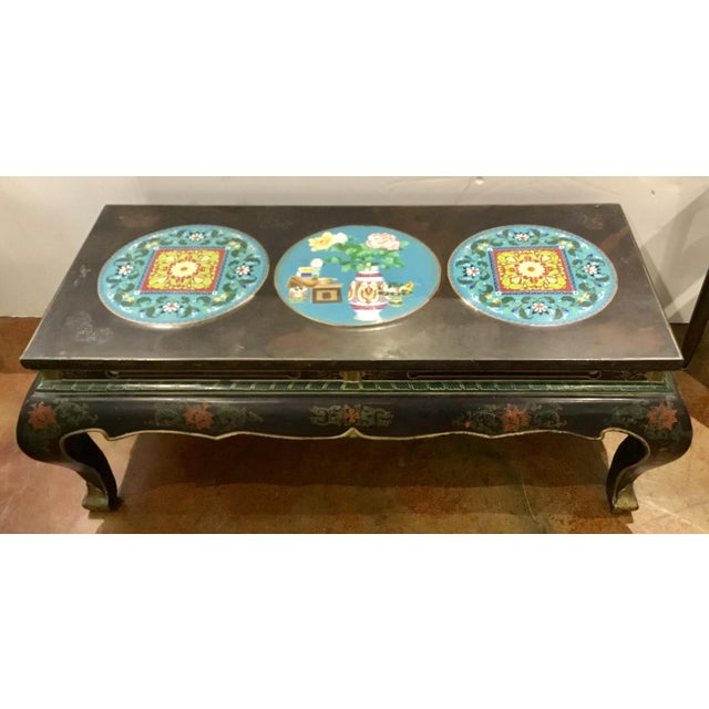 Elegant antique Asian 1920's Cliosionne cocktail table, black frame trimmed in gold with three medallions, flowers on the...
