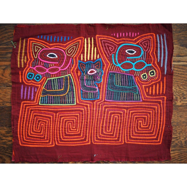 -Brightly colored tribal art depicting three animals of some sort. Made by the Mola people from Colombia or Panama....