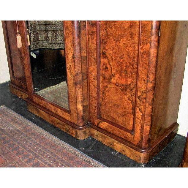 This is a late 19th Century circa 1870, burl walnut breakfront wardrobe. It has 3 doors, the 2 side doors open to reveal...