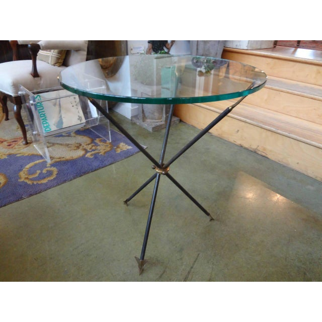 Chic Italian mid-century modern iron and brass/bronze tripod gueridon with arrow design and a new glass top. Made in the...