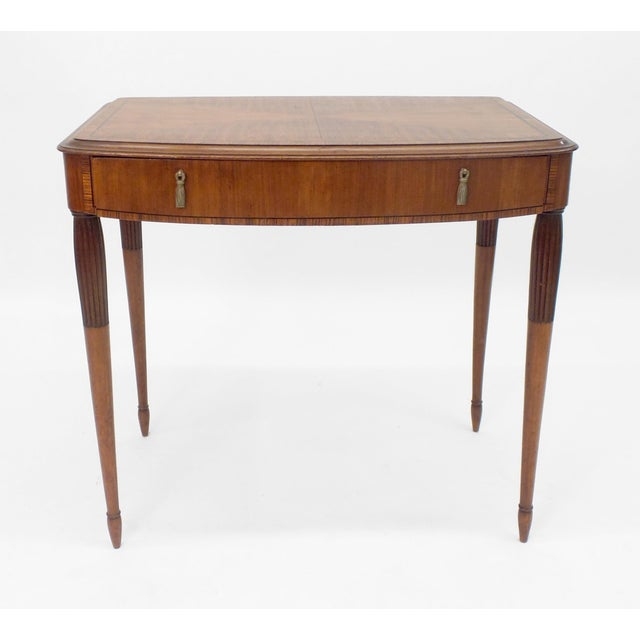 An Art Deco period side table having walnut and Coromandel wood veneers with ebony inlays. One drawer with brass drop...
