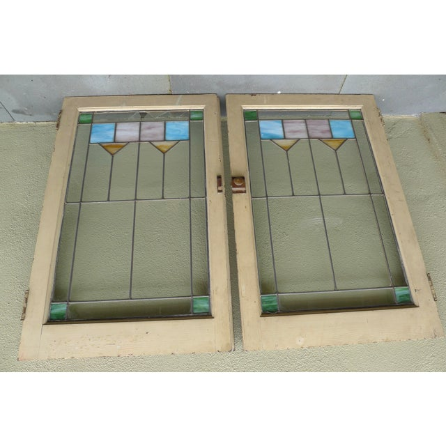 Lovely set of stained glass windows from the Arts & Crafts period, circa 1920. These windows feature a simple geometric...