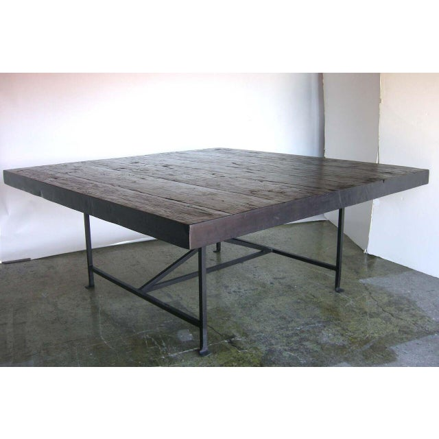 """Reclaimed 100 year old wood atop hand forged iron base. Wonderful naturally distressed, dark wood top. 3.5"""" thick boards...."""