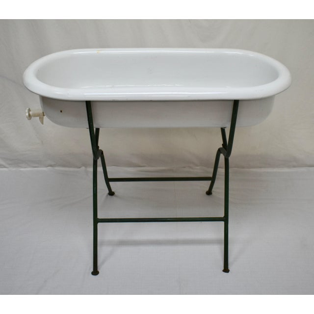 This is a vintage porcelain enamel baby bath on its original wrought iron folding stand. This is a particularly nice...