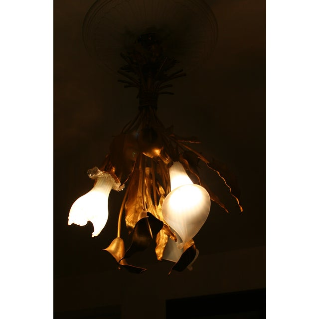 The chandelier modeled as a tied bunch of Lillies and leaves with three Lilly head milk glass shades, wired for...