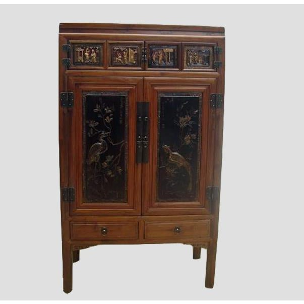 This cabinet has a beautifully carved crane and phoenix on each door panel with eight figures carved on the top of the...