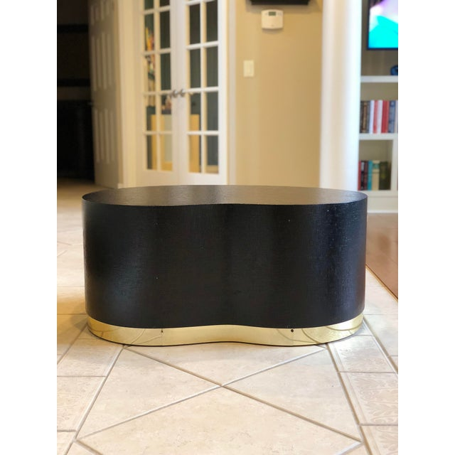 Fabulous free form kidney table in a lacquered black grass cloth finish with a brass band base. A statement piece in the...