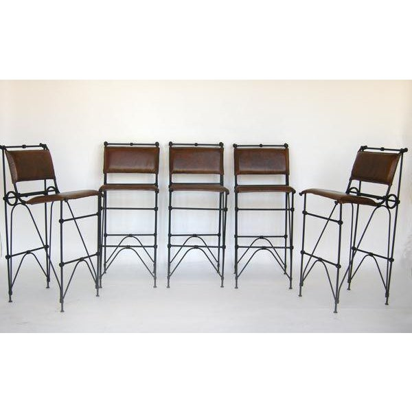 Set of five vintage bar stools by Israeli born artist and designer Illana Goor. Iron and leather. Sewn edge detail on seats.