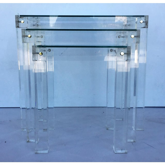 These Mid-Century Modern nesting tables embody the 1970s. They are comprised of a Lucite frame joined by connectors and a...