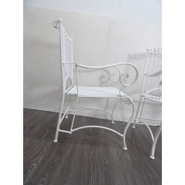 Ornate Pair of Iron Patio Chairs. This pair are vintage but have been refinished in a new White Lacquer. The Chairs are...