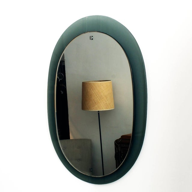 Beveled mirror with a gray-green glass frame, chrome-plated brass hardware, original oxidation. Italy, circa 1960.