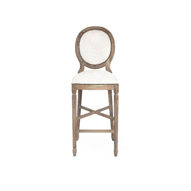 Round back counter stool upholstered in Brazilian white cowhide on limed grey oak frame.