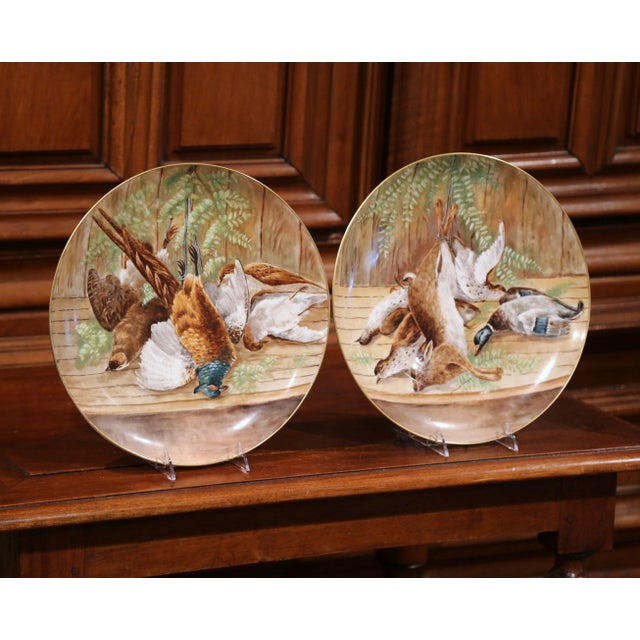 This fine pair of antique wall hanging plates were crafted in France, circa 1880. Each hand-painted porcelain plate...