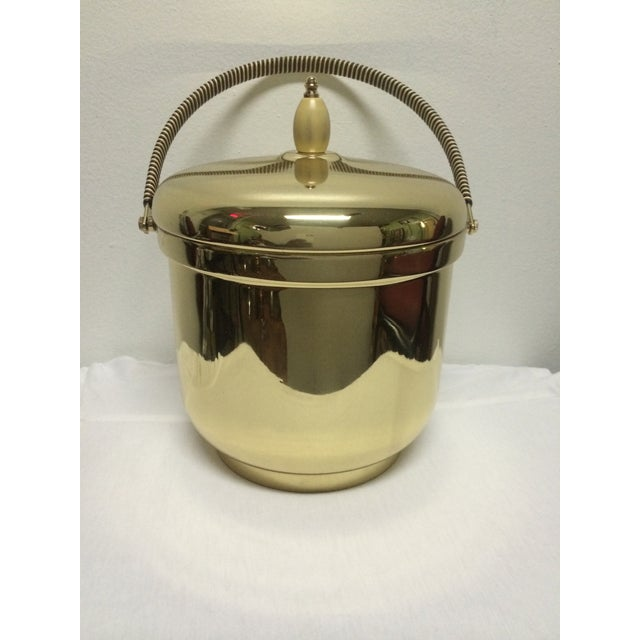 This brass ice bucket has been restored and polished. It has a mercury glass interior.