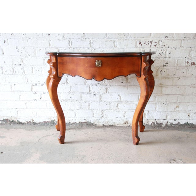 Offering a beautiful Baker Furniture maple French console table. Each table has a beautiful maple finish with darker...