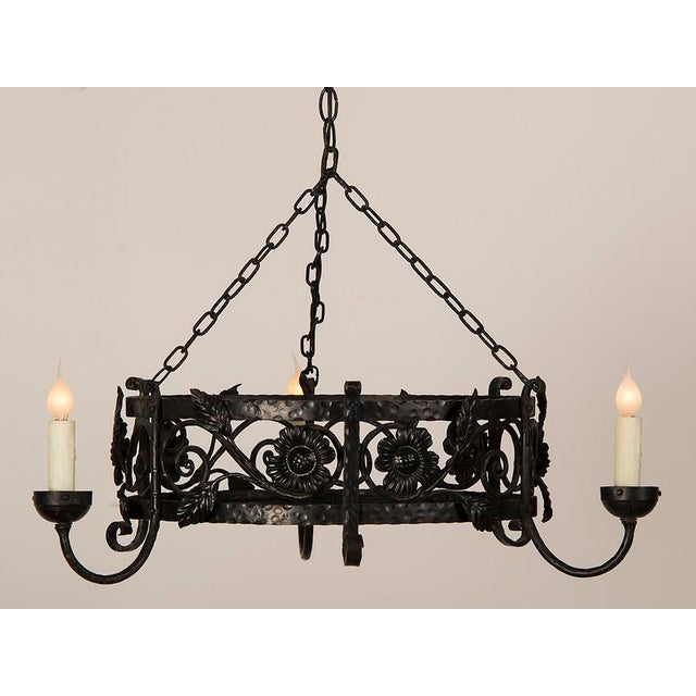 A large three light circular painted iron chandelier from France c. 1930 with a profusion of floral decoration on the...