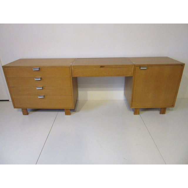 A three piece combed oak vanity set including middle light up mirror with storage, four drawer chest and one door storage...