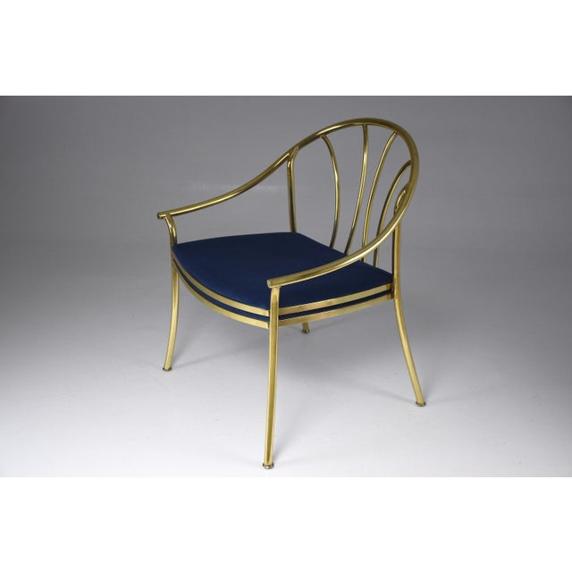 A beautifully crafted 20th century French vintage armchair composed of polished solid gold brass and designed with a curve...