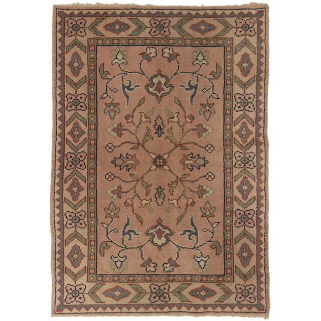 An antique, Turkish, oushak rug that features hand knotted wool. This has a beautiful color and tone variations.