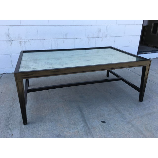 Gorgeous and elegant ebonized black frame coffee table with antique mirror top. Great detailing on the solid walnut frame,...