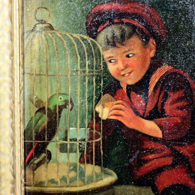An antique oil on canvas genre painting depicts street urchin boy feeding his caged parrot, artist signed lower right,...
