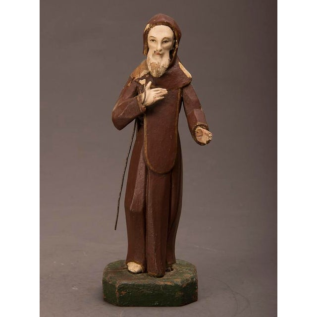 A carved and painted wooden statue of St. Francis of Assisi from 19th century Spain.