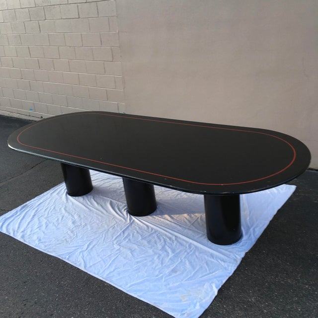 Vintage black lacquered racetrack (elliptical) dining or conference table, with red pin stripe, and tri-pedestal...