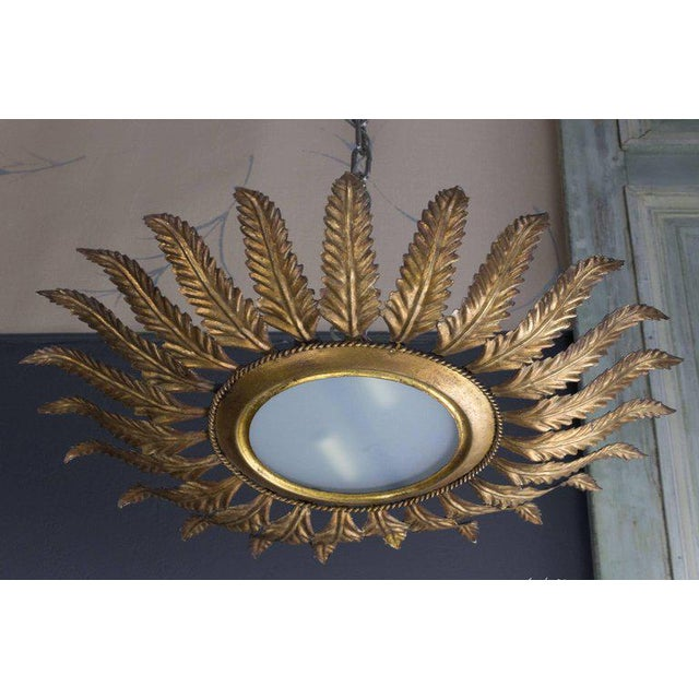 """Spanish 1940s gilt sunburst ceiling fixture with decorative leaves connected to small braiding. Measures: 24"""" diameter. UL..."""