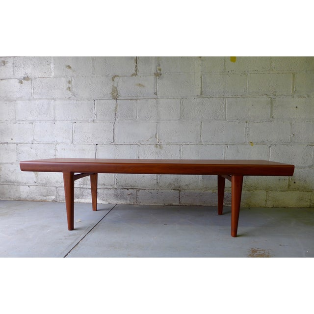 Long and sleek teak mid century modern styled coffee table with gorgeous wood grains and two hidden cubbies underneath the...