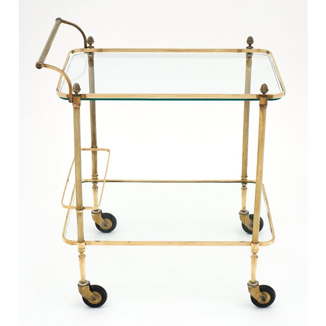 French Art Deco period bar cart with finials. This elegant, simple, and very sturdy piece features two shelves, a handle,...