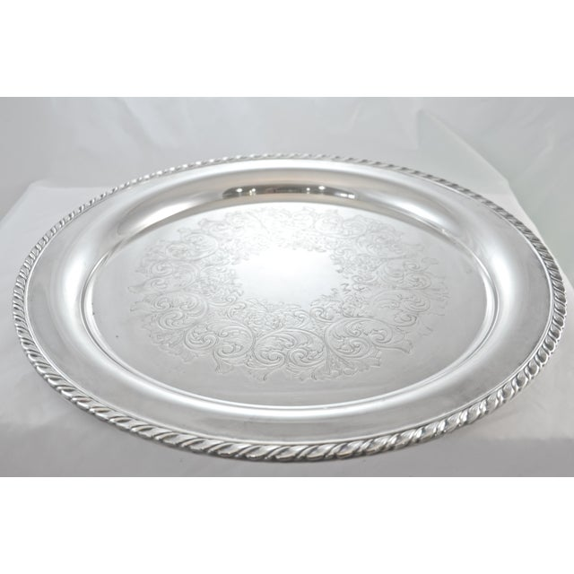 """Large round silver plate tray with gadroon rim and floral-scrolled center. Labeled """"Wm. A. Rogers, by Onieda Ltd..."""