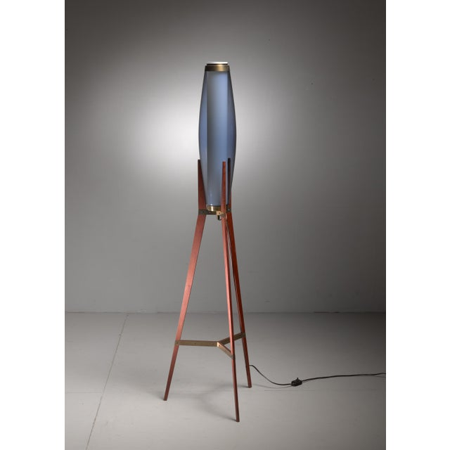 A tripod floor lamp by Danish designer Svend Aage Holm Sørensen. The lamp is made of a teak frame with brass elements. The...
