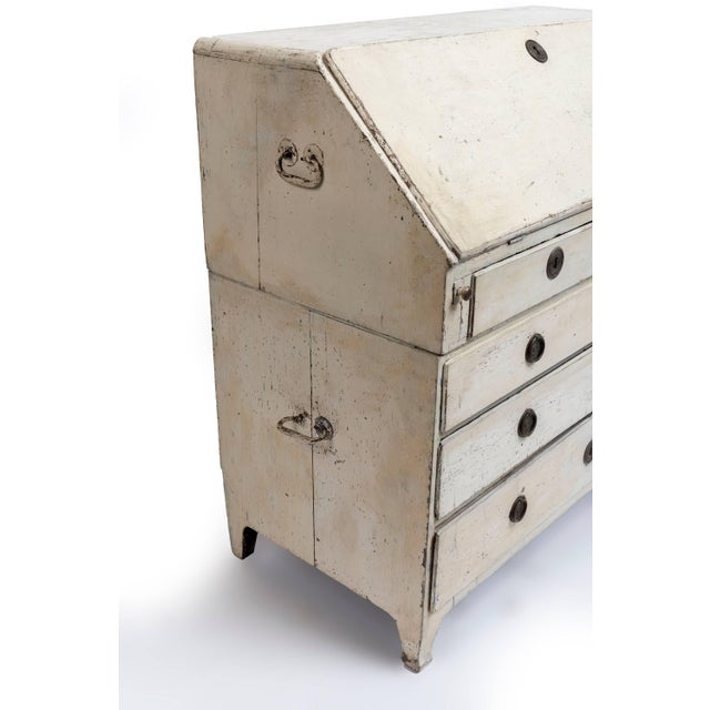 A white painted 19th century, Swedish scriban with several drawers and pockets with drop down front.
