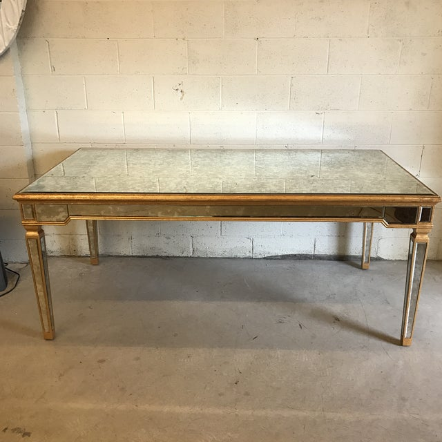 Beautiful, slightly smoked antique mirror completely covers this dining table. Its accented with gold leaf all around....