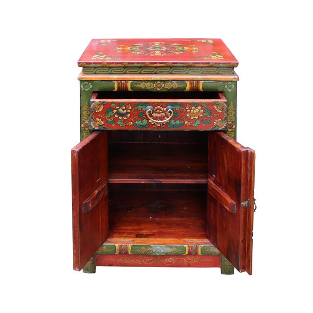 This cabinet/table is painted with colorful (green rim and orange yellow base ) Tibetan style flower graphic at front, the...