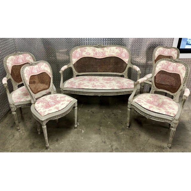 A set of 19th Century Louis XV chairs and matching settee, in the original cane but reupholstered in sweet pink toile....