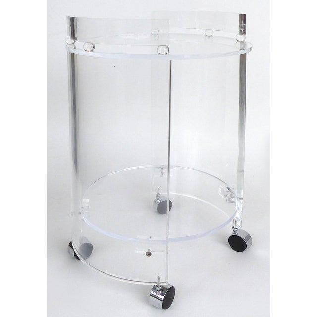 Offered for sale is a tall two-tiered round Lucite bar cart on casters. The cart incorporates both substantial Lucite...