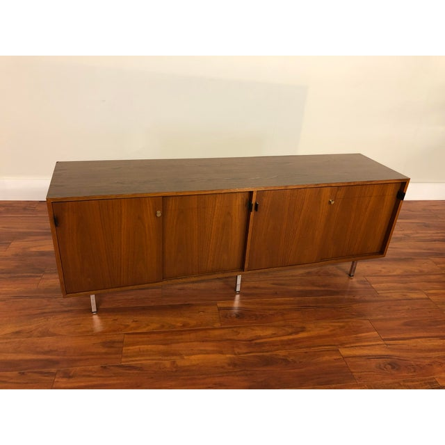 Vintage Florence Knoll four position credenza with leather pulls, circa 1960s. It features four sliding doors with four...