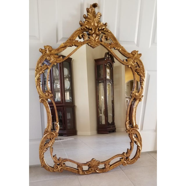This is a large mid-19th century Italian Baroque Style Carved Giltwood Estate Mirror. Featuring a carved scroll motif...