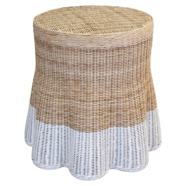 "A woven wicker table falling to a scalloped, skirt-like draped bottom, dipped in paint. The top is 20"" round. Each design..."