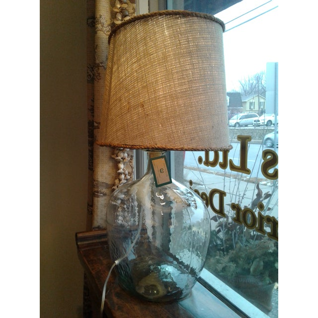 As chic as it is simple, this contemporary mouth-blown glass table lamp top with brown burlap shade offers a summer beach...