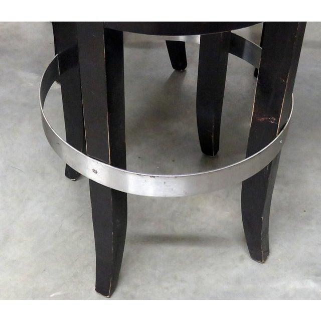 4 Mid-Century Modern swiveling bar stools with ebonized frames and leather upholstery.